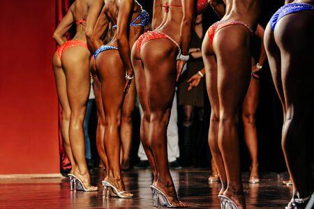groeps vrouwelijk fitnessmodel dat haar en slanke benen poseert Stockfoto