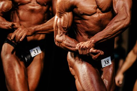 muscular athletic bodybuilder posing biceps on hand in bodybuilding competition