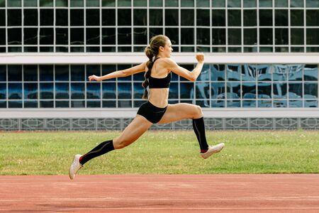 triple jump women athlete on stadium in background black glass facade building Stok Fotoğraf