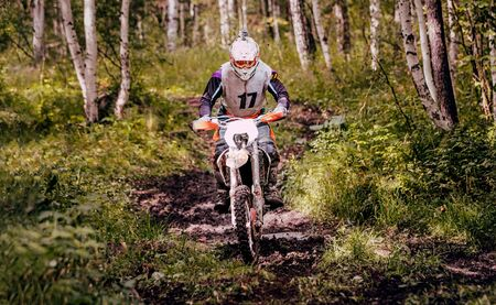 motocross enduro rider riding on muddy forest trail