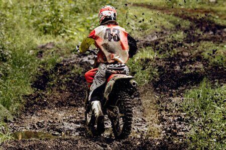back motocross enduro rider. splashes lumps of dirt