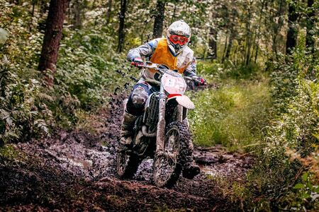 motocross enduro racer riding on wet and muddy forest track