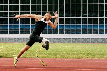atleta corridore disabile fisico correre sulla pista dello stadio