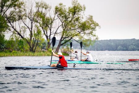 group athletes kayakers competition race in rowing on kayak