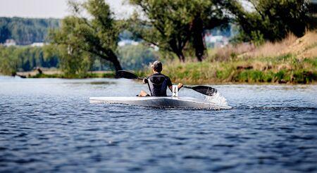 back athlete kayaker rowing in lake. kayak competition race 写真素材
