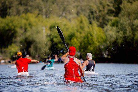 back group kayaker athletes kayaking race on lake