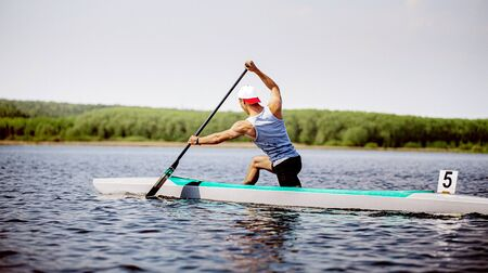 men canoeist rowing in lake. canoeing competition race