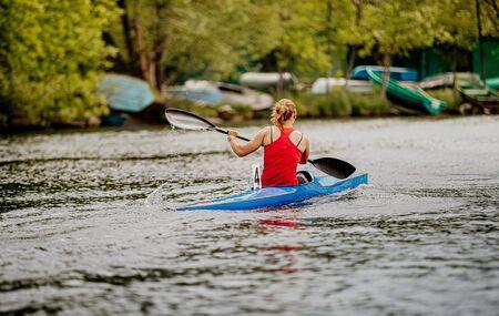 back kayaker woman rowing on blue sports kayak