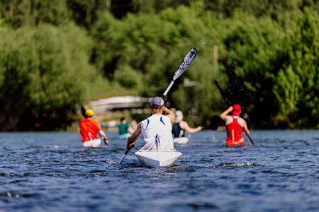 back group young athletes rowers kayaking on lake
