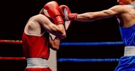 Boxer landet mit dem linken Jab, um durch seine Handschuhe zu gehen Standard-Bild