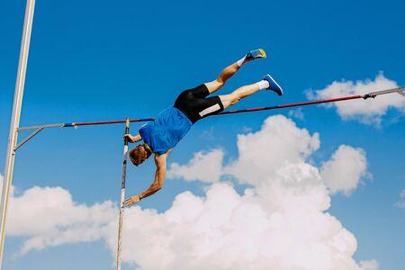 Athlet Stabhochspringer im Stabhochsprung Wettbewerb Hintergrund blauer Himmel