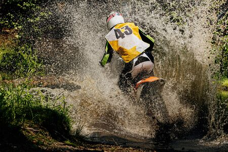 back rider enduro motorcycle riding puddle of water and mud, splashes and drops Reklamní fotografie