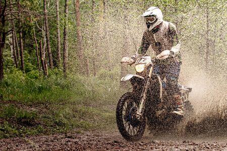 rider on enduro motorcycle riding splash on water and mud