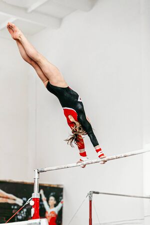 young woman gymnast exercise on uneven bars in gymnastics