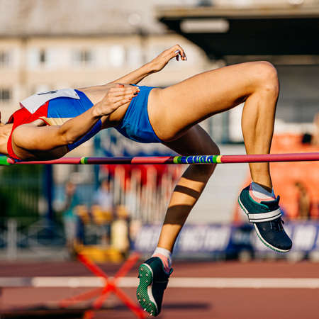 women athlete jumping high jump in athletics competition