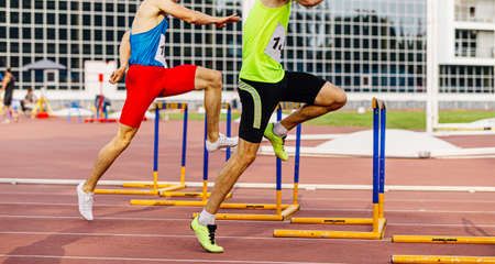 male athletes run hurdles at stadium in athletics competition Banque d'images