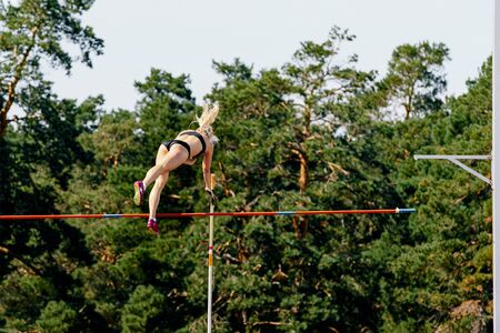 pole vault woman athlete jump on background of forest