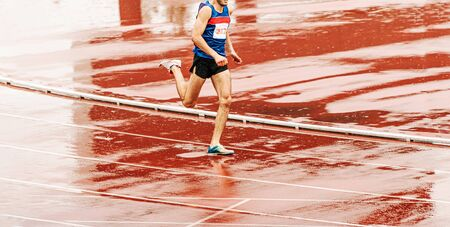 man runner running on wet track in rain at athletics competition