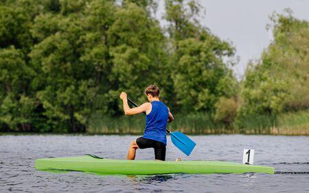 canoe single men paddles on lake in canoeing sprint