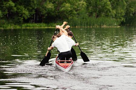 back four athletes canoeist paddling in canoe on lake
