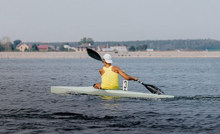 kayak single men paddles on lake in canoeing sprint