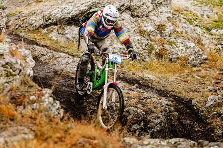 dirty rider riding on autumn trail in downhill race