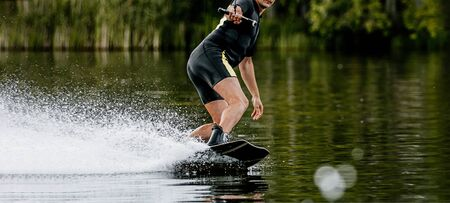 man wakeboarding on summer lake. water splashes from under board