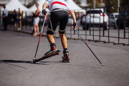 back man skier in roller skiing race