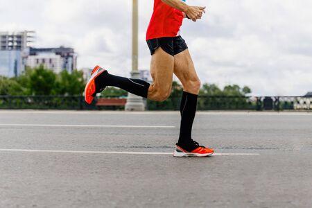 穿着黑色压缩袜的男子跑城市马拉松