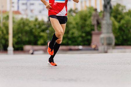 男子跑步者在黑色压缩袜跑城市马拉松