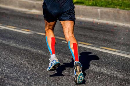 kinesio tapipng on calf muscle of athlete runner running on dark asphalt