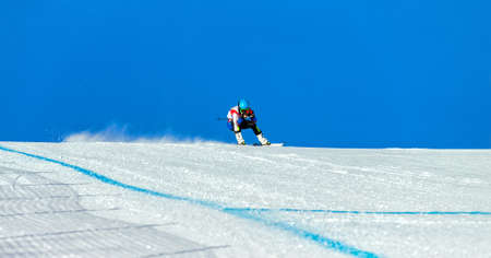man mountain skier on track of giant slalom in background blue sky