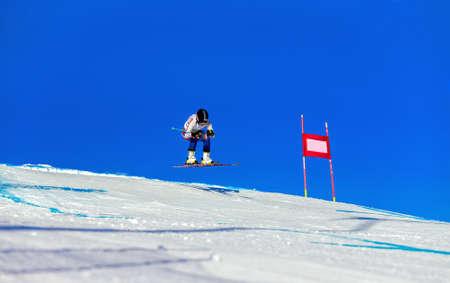 female downhill skier on track of giant slalom in background blue sky