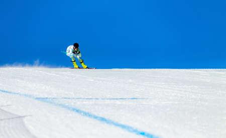alpine skier athlete on track of giant slalom in background blue sky