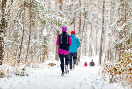 athletes runners running winter trail marathon in forest during a snowfall