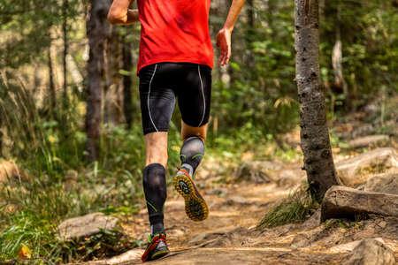 back man runner in compression socks running forest stones trail Banque d'images