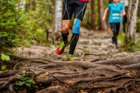 legs man runner in compression socks and kinesio taping on knee run forest trail