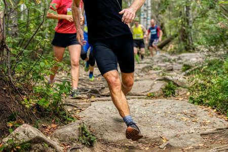 group runners athletes run on rocks forest trail marathon