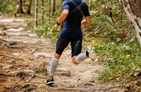 man athlete runner run forest trail over rocks and tree roots