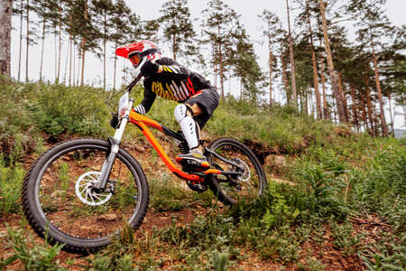 downhill mountain biker on forest trail. competition DH Banque d'images