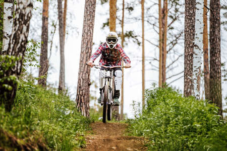 athlete mountain biker on forest trail in competition downhill Banque d'images