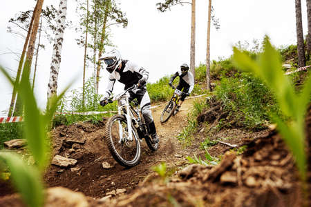 two downhill mountain biker on forest trail. rides competition DH