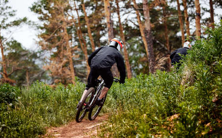 downhill mountain rider athlete rides on trail in forest