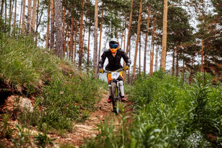 downhill rider athlete rides race on trail in pine forest