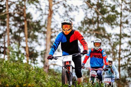 three rider athlete on downhill mountain biking trail