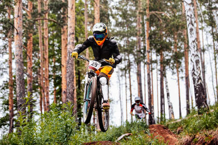 athlete downhill bike rides race on trail in pine forest