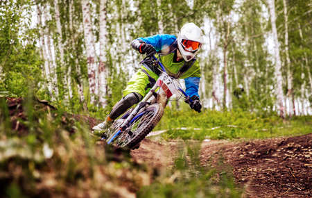 athlete mountain biker riding turn in forest trail