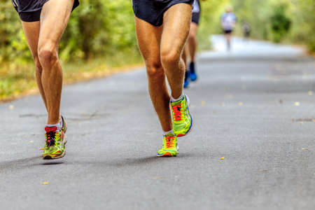 Chelyabinsk, Russia - September 11, 2016: legs two male runners in running shoes Asics in City marathon