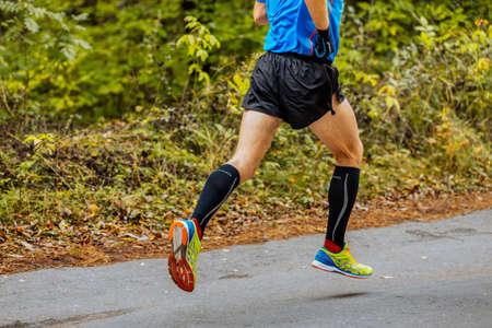 Chelyabinsk, Russia - September 11, 2016: legs man athlete runner in running shoes Asics Gel DS Racer 10 in City marathon