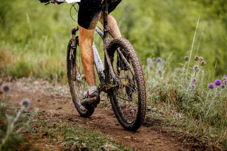 close up cyclist dirty feet and mountain bike riding on trail
